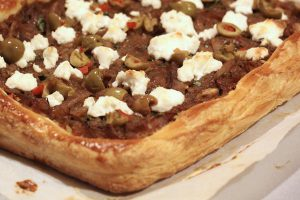 Olive tapenade tart with caramelized onions and ricotta cheese