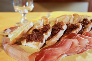Prosciutto and toasted bread with tapenade and olive oil