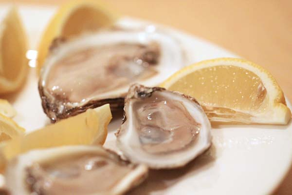 Shucked oysters with lemon wedges