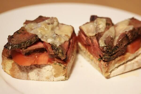 Open-face flank steak sandwich with goat cheese and tomato
