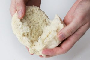Splitting a freshly-baked sourdough English muffin