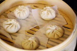 Steaming Chinese pork buns in a bamboo steamer
