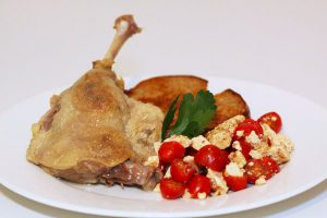 Homemade duck confit with toast and tomato-feta salad