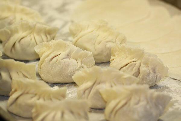 Lining up Chinese pork and shrimp dumplings (jiao zi)