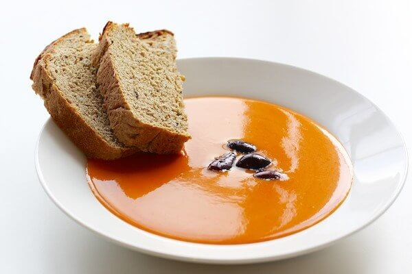 Cold tomato and red pepper soup with bread and olives