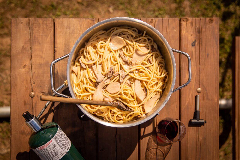 Vegan mushroom cream sauce pasta on a camp stove on a picnic table