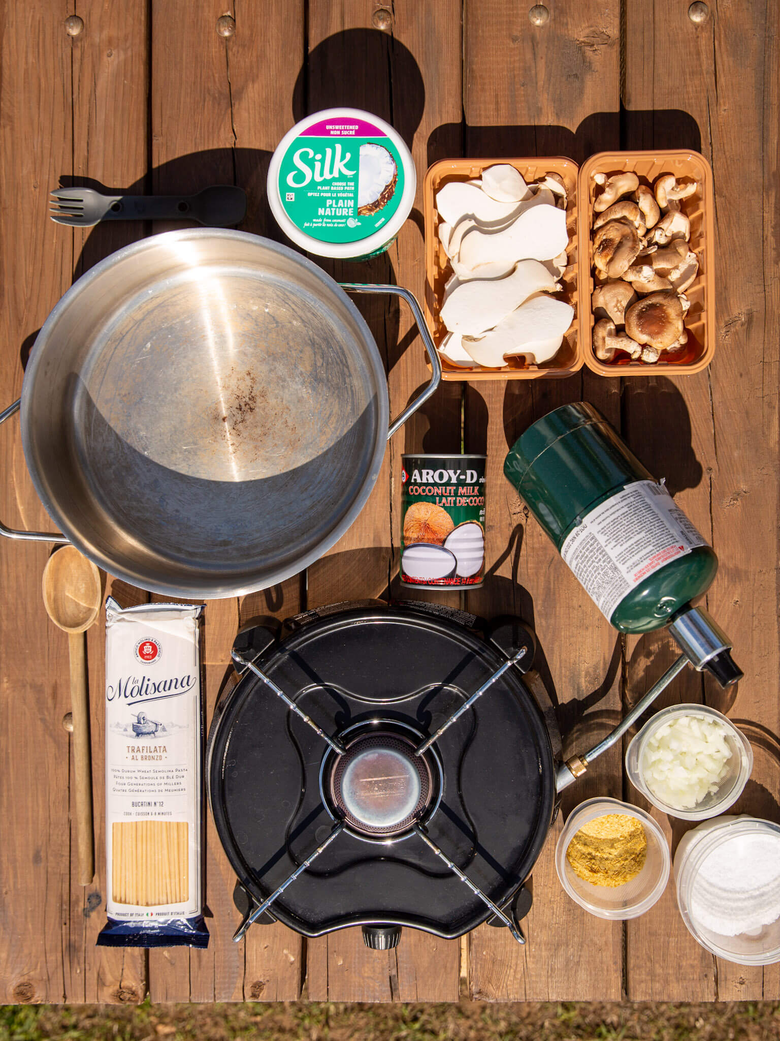 Ingredients for vegan mushroom cream sauce pasta laid out on a picnic table